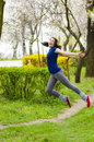 Woman enthusiasm a happy young jumping i a park Stock Images