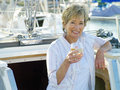 Woman in entrance to cabin of boat with drink smiling portrait Royalty Free Stock Photo