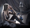 A woman in erotic lingerie smoking a hookah Royalty Free Stock Photography