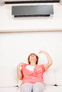 Woman escapes from the heat under the air conditioner at home happy mature on sofa Royalty Free Stock Image