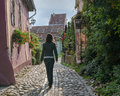 Woman on european cobblestone street walking a flower lined in the transylvanian medieval citadel of sighisoara romania Royalty Free Stock Photos