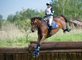 Woman eventer on horse is Drop fence in Water jump Royalty Free Stock Photography