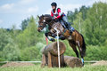 Woman eventer on horse is overcomes the Log fence Stock Image