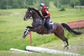 Woman eventer on horse is overcomes the open ditch Royalty Free Stock Photos