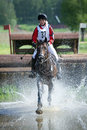 Woman eventer on horse is run in Water jump Stock Photography