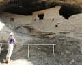 A woman examines cave at the gila cliff dwellings in rock face national monument new mexico Stock Images