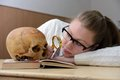 Woman examining a human skull Stock Photo