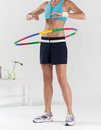 Woman exercising with colorful plastic hula hoop Royalty Free Stock Photo
