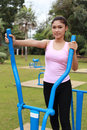 Woman exercising with exercise equipment in the pa public park Stock Photos