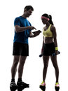Woman exercising fitness man coach using digital tablet one women workout with men in silhouette on white background Stock Photos