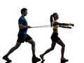 Woman exercising fitness resistance rubber band with man coach one women workout men in silhouette on white background Stock Photo