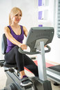 Woman exercising in gym on a stationary bike Royalty Free Stock Images