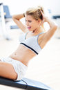 Woman exercising in a gym working out at health club Royalty Free Stock Image