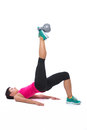 Woman exercising with kettlebell young lying on back on foot white background Stock Photography