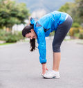 Woman exercising outdoors fit stretching and looking happy Royalty Free Stock Image