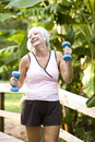 Woman exercising in park walking with hand weights Royalty Free Stock Photos