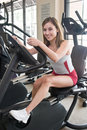 Woman Exercising On Stationary Cycle Stock Images