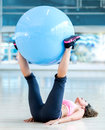 Woman exercising with a swiss ball fit at the gym Stock Photography