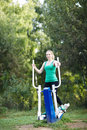 Woman exercising on a trainer healthy fit young in the garden vertical shot Royalty Free Stock Photography