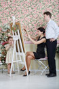 Woman explains her plan to artist and little girl stands behind easel in beautiful retro interior Royalty Free Stock Photos