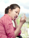 Woman expressing displeasure with cellphone and getting mad at the phone Royalty Free Stock Photos