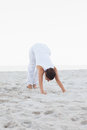Woman in extended triangle yoga pose doing at the beach Royalty Free Stock Image