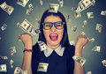 Woman exults pumping fists ecstatic celebrates success under money rain Royalty Free Stock Photo