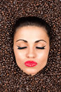 Woman face with closed eyes in the coffee beans Royalty Free Stock Photo