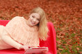 Woman in fall park with tablet browsing internet. Royalty Free Stock Photo