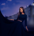 Woman in fashion black dress in the night city beautiful with long hair magic Royalty Free Stock Images