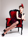 Woman with fashion hairstyle and red armchair beautiful adult poses at studio Royalty Free Stock Images