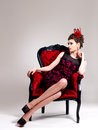 Woman with fashion hairstyle and red armchair beautiful adult poses at studio Royalty Free Stock Image