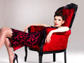 Woman with fashion hairstyle and red armchair beautiful adult poses at studio Royalty Free Stock Photos