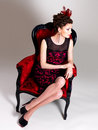 Woman with fashion hairstyle and red armchair beautiful adult poses at studio Royalty Free Stock Photo