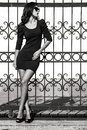 Woman fashion young in tight dress lean on wrought iron fence full body shot bw Royalty Free Stock Photos