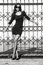 Woman fashion young in tight dress lean on wrought iron fence full body shot bw Royalty Free Stock Image
