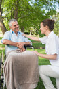 Woman with father sitting in wheel chair at park her mature the Stock Image