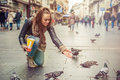 Woman feeds pigeons on the street