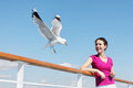 Woman feeds seagulls with bread on deck of ship. Royalty Free Stock Image