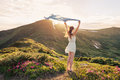 Woman feel freedom and enjoying the nature in mountains with blue tissue in hands on sunset Stock Photo