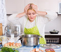 Woman feeling bad smell from pan unhappy blonde housewife preparing exotic food with rank odour at kitchen Stock Photo