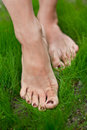 Woman feet on the grass green Stock Photos