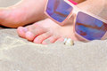 Woman feet with natural nails on beach with funny sunglasses a lot of copy space forefround Royalty Free Stock Photos