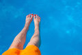 Woman feet over a swimming pool Royalty Free Stock Photo
