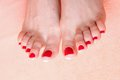 Woman feet with red toenails on towel pink Stock Photo