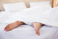 Woman feet under a duvet at home Royalty Free Stock Photography