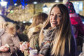 Woman on the festive Christmas market at night. Happy woman Feeling the urban christmas vibe at night. Royalty Free Stock Photo