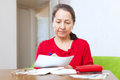 Woman fills in payment documents serious mature at home Royalty Free Stock Photography