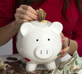 Woman fills savings piggy bank american currency cash coins female hand with Royalty Free Stock Photography