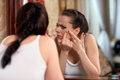 Woman finding an acne on her cheek Royalty Free Stock Photo